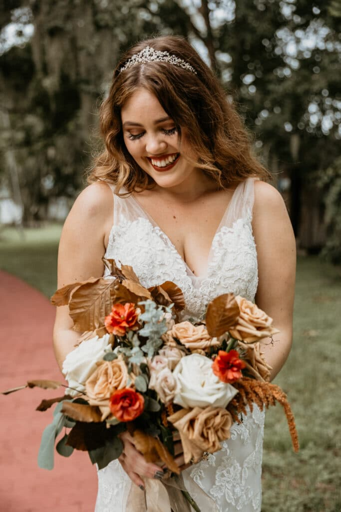 bride on brick pathway looking down at her bouquet with fall color flowers