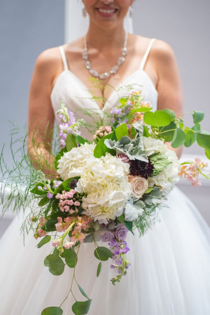 bride holding large bouquet with big white flowers, small pink and purple flowers and cascading leaves