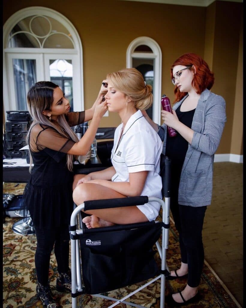 bride sitting cross legged in chair getting hair and makeup done by About Face Design Team