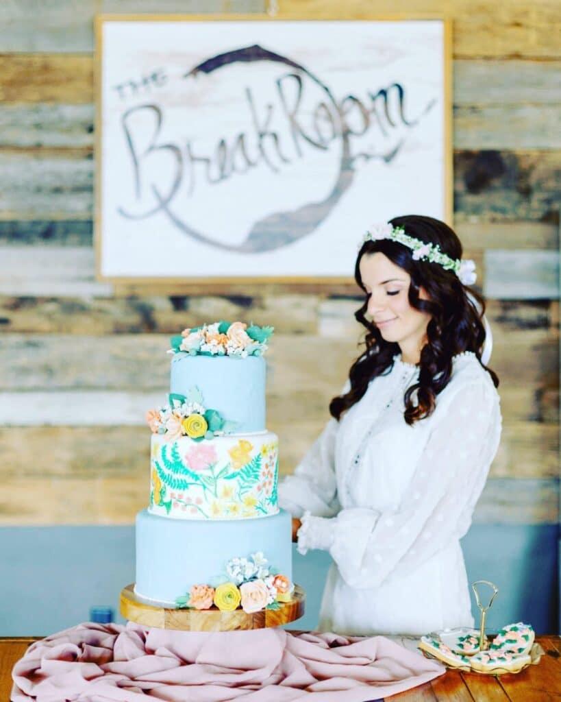 bride standing next to three tier wedding cake