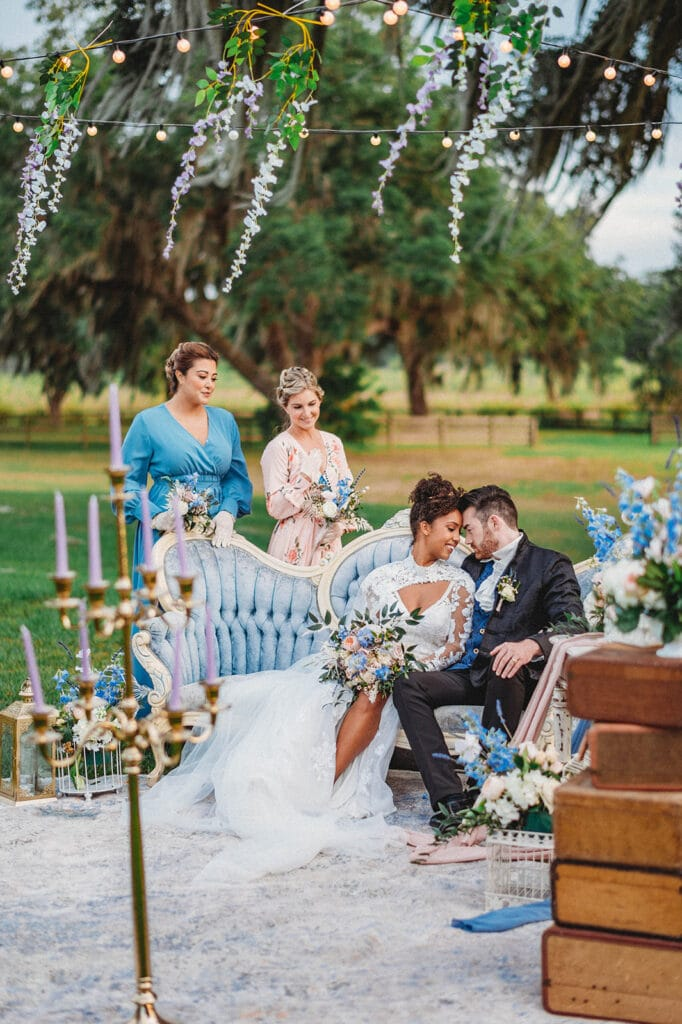 bride and groom sitting on blue couch outside with bridesmaids behind them