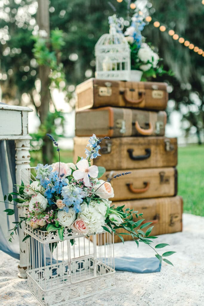 bird cages filled with flowers and old luggage as decoration from Wonderstruck Wedding and Event Planning