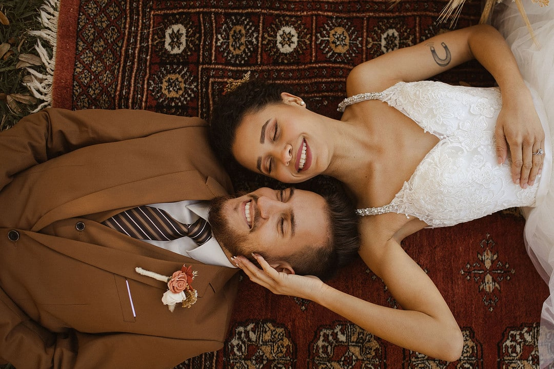 bride and groom in neutral tones laying next to each other