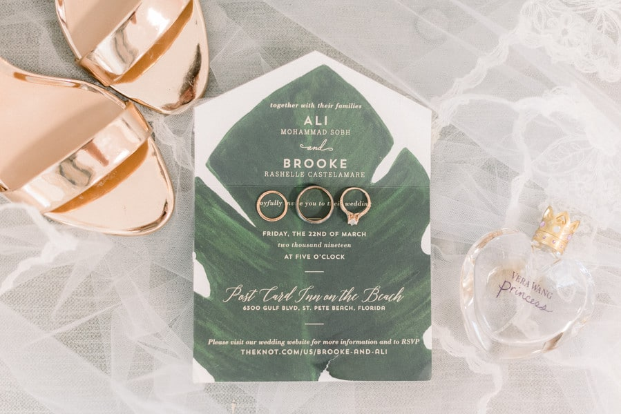 the wedding invitation with the wedding rings on top and the bride's shoes in the corner