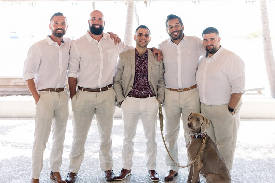 the groom and his groomsmen and dog standing together and smiling