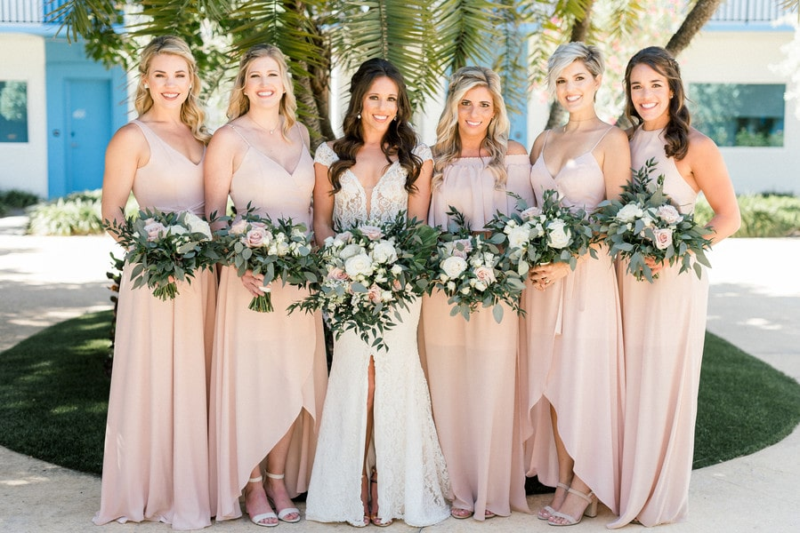 the bride and her bridesmaids standing together holding their bouquets and smiling