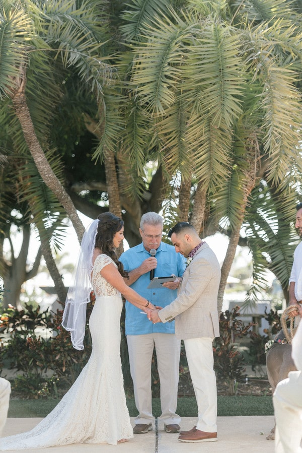 the bride and groom holding hands while the officiant speaks into the microphone at their wedding