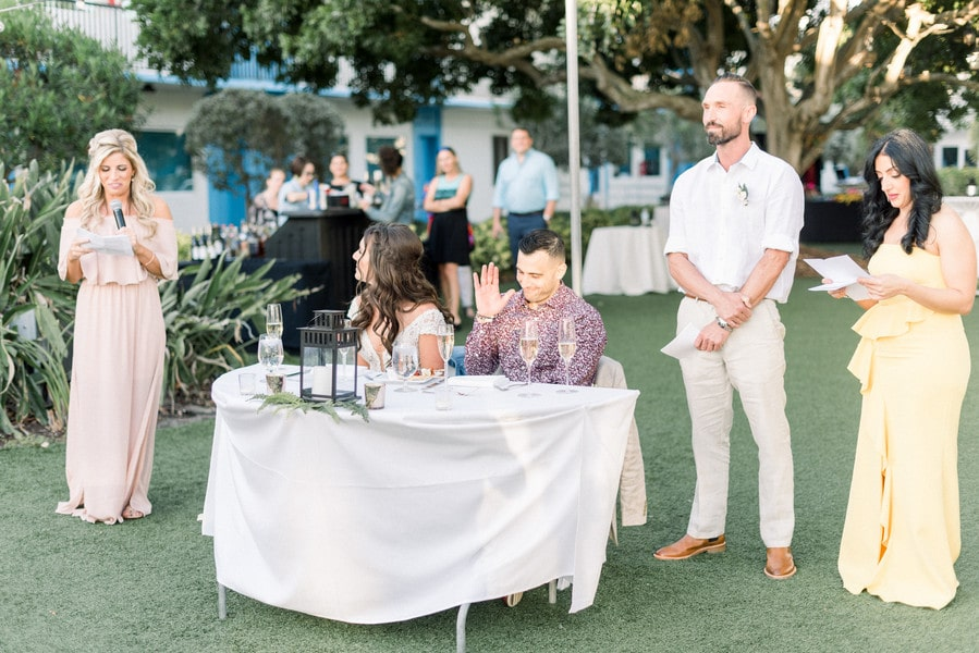 a bridesmaid giving a speech for the new married couple while they sit at their sweetheart table