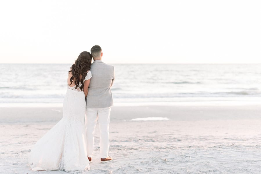 bride and groom facing the ocean while the bride lays her head on her husband's shoulder