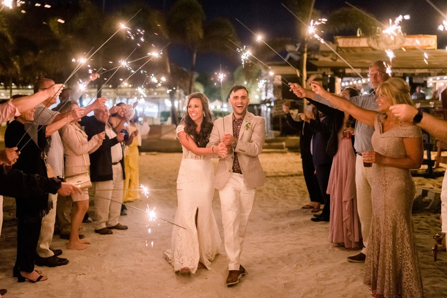 bride and groom walking while the guests hold sparklers above their heads to end the night