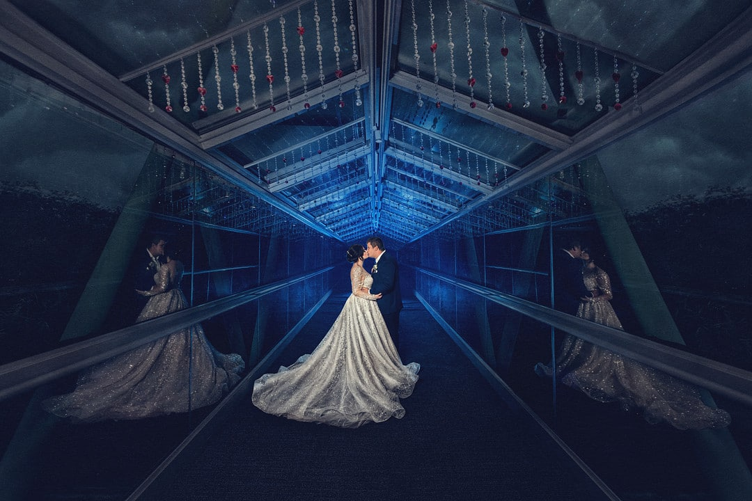 bride and groom kissing with a blue light behind them in a catwalk