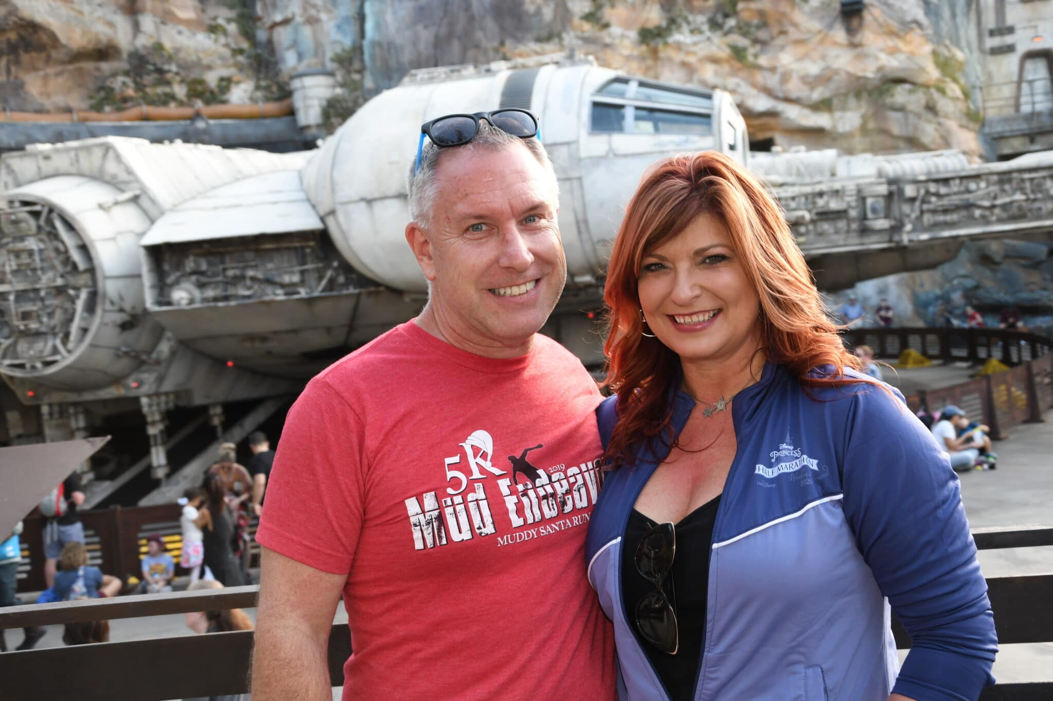 bride and groom to be smiling at the star wars section of disney