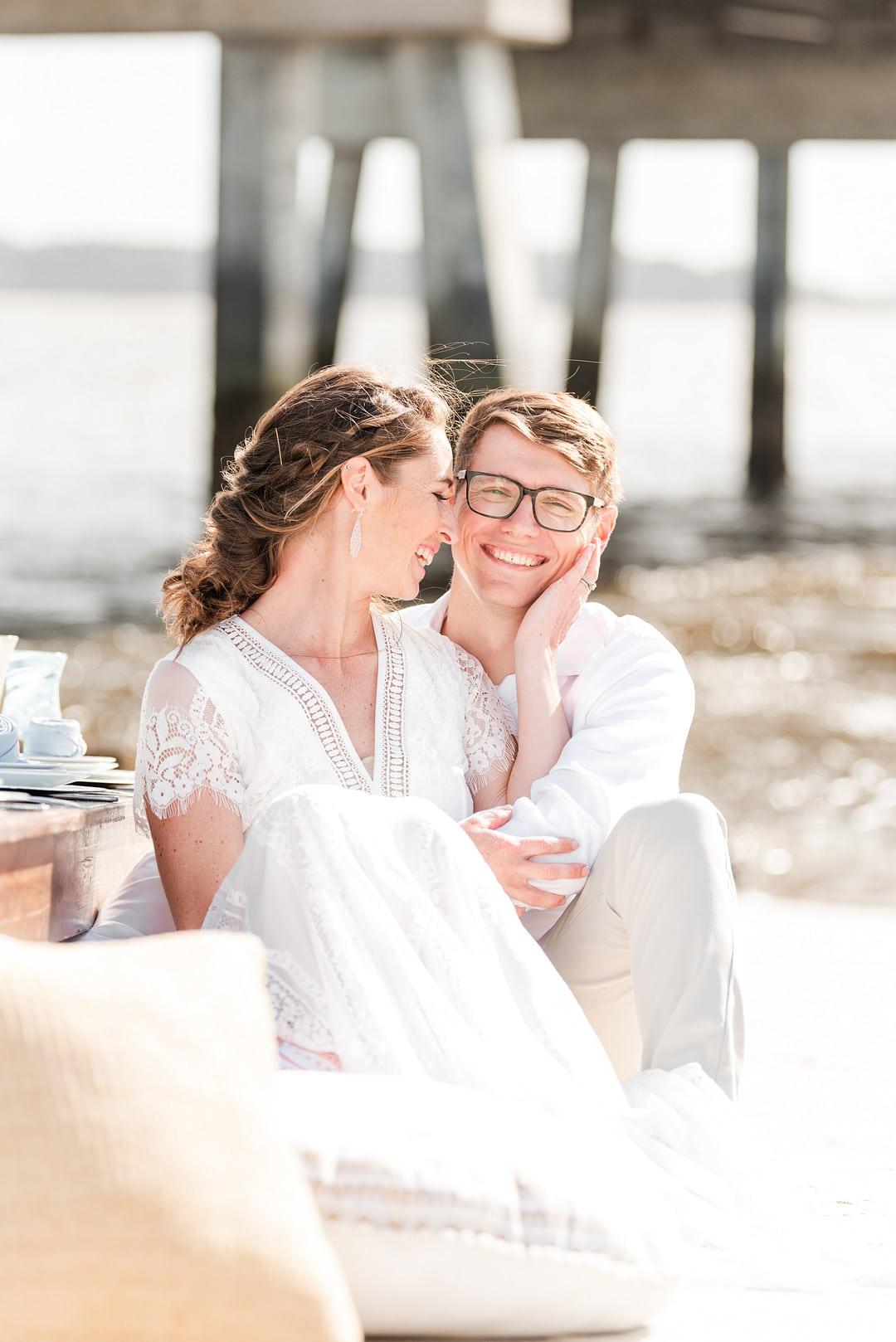 bride and groom cuddling on the beach for the amelia island beach wedding inspiration shoot