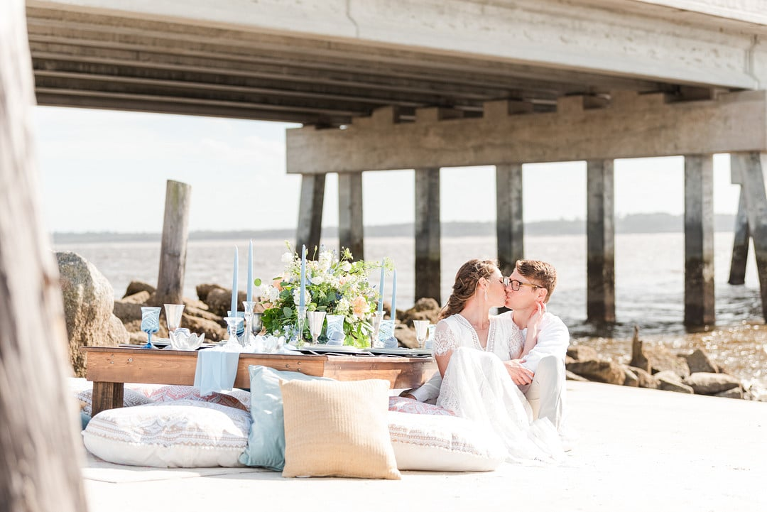 bride and groom sitting next to their reception table kissing for the amelia island beach wedding inspiration shoot