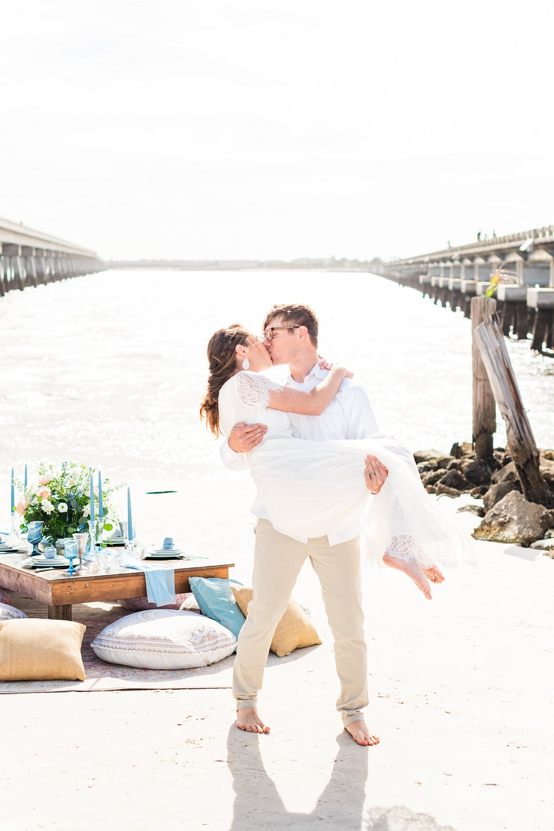 groom holding the bride in his arms while kissing next to the beach and their reception table