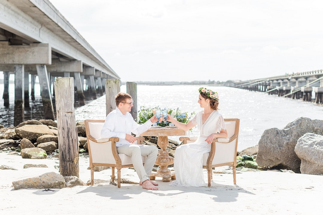 the bride and groom sitting in two gold and white antique chairs