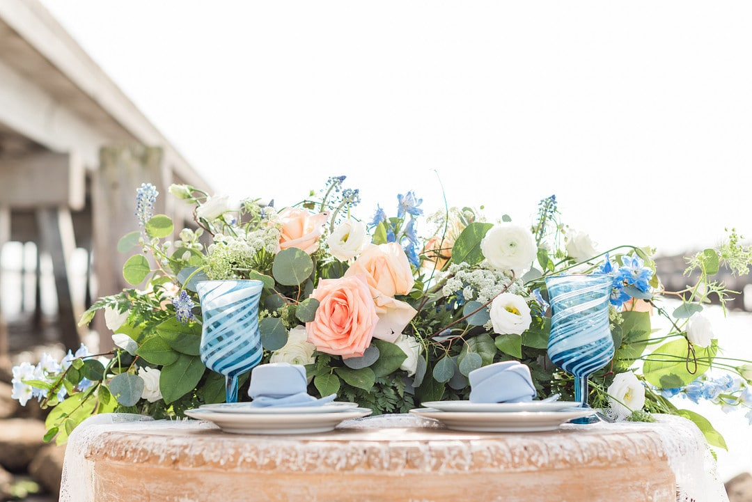 the sweethearts table with blue, pink, and whit florals and two blue glasses next to stacks of plates