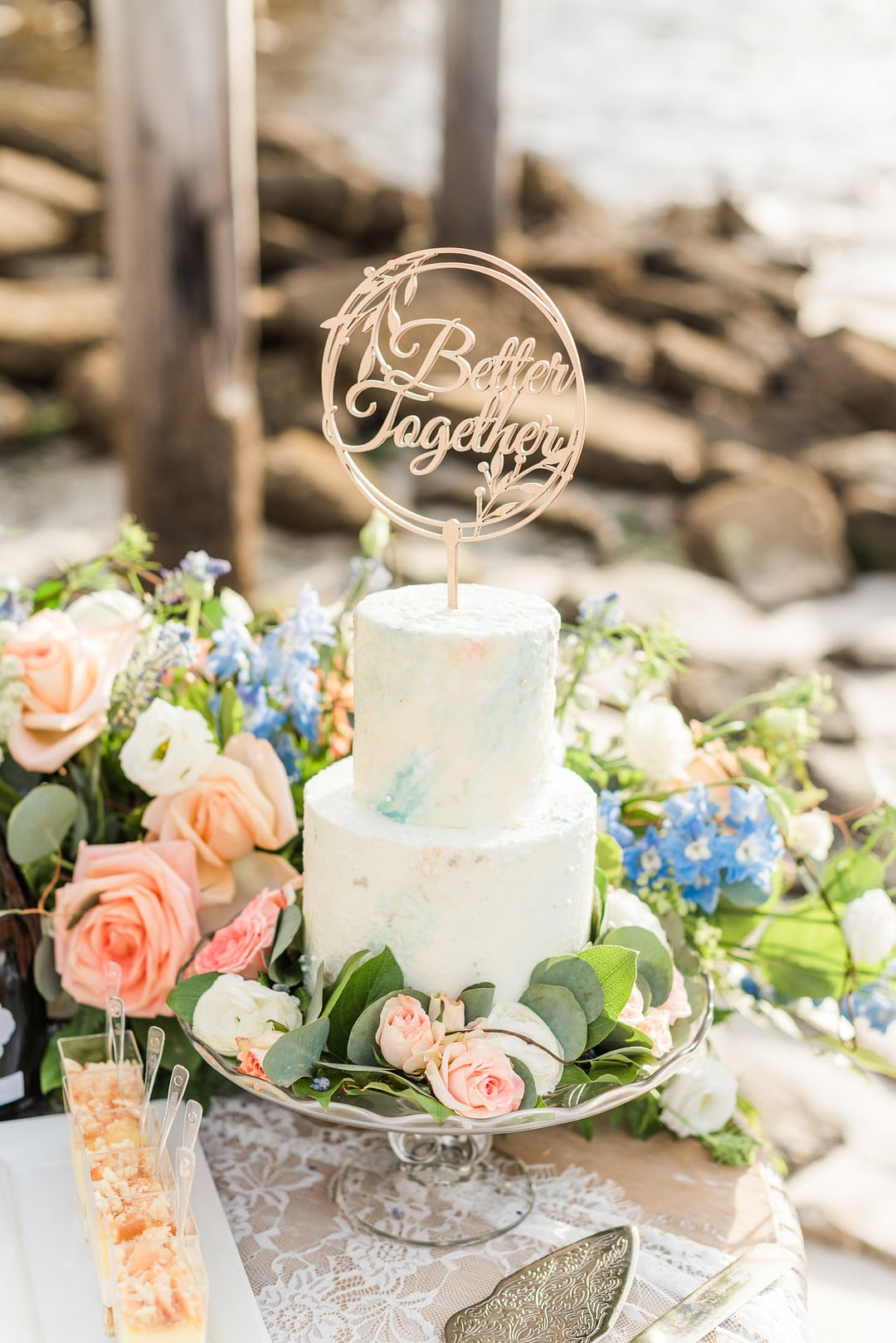 two tier blue and white cakes with florals and greenery surrounding
