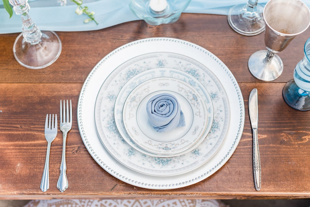the plates stacked on one another with a blue napkin wrapped into a rose in the center