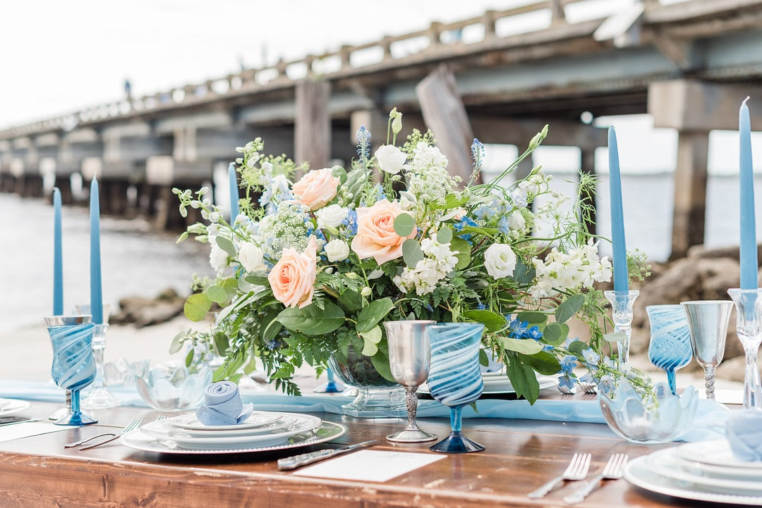 the table center piece surrounded by the blue glasses and the beach in the background
