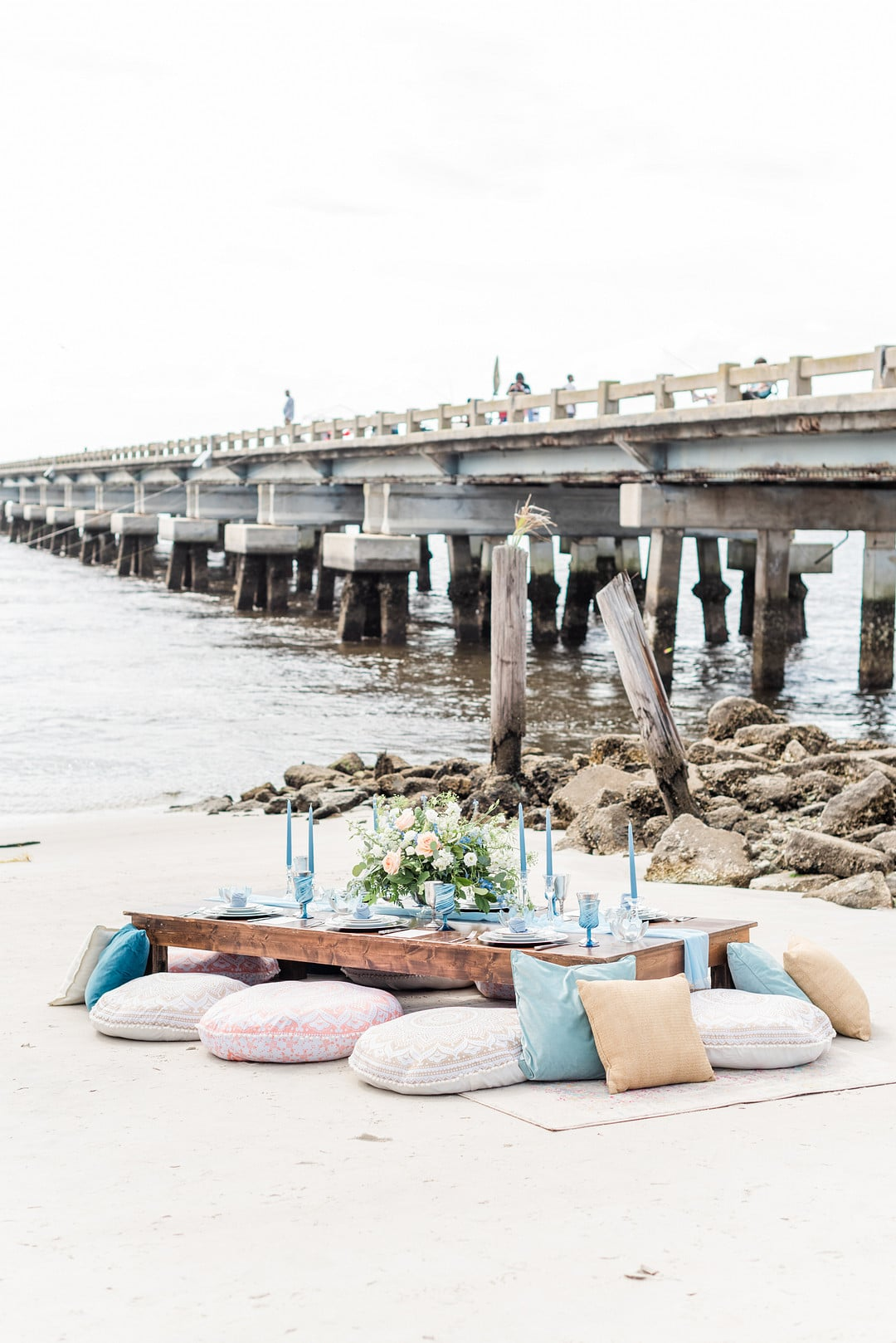 the table set up with pillows as chairs on the beach with a dock in the background