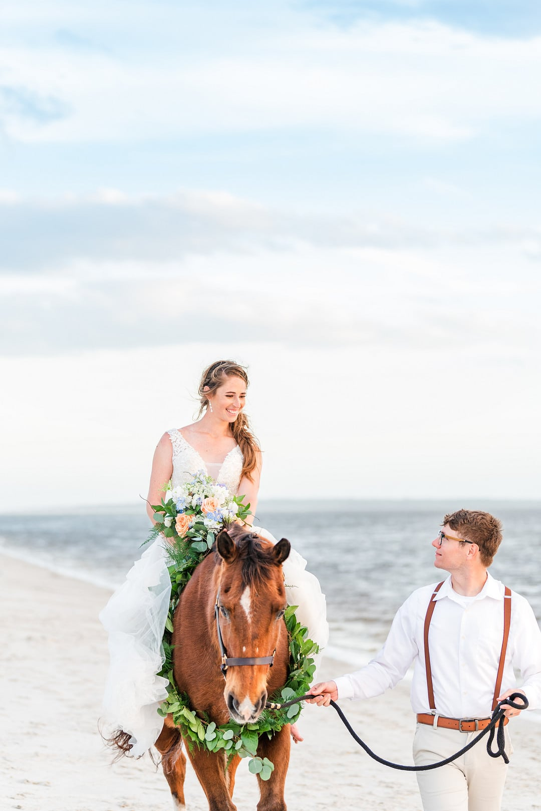 bride riding down the beach on her horse while the groom walks the horse