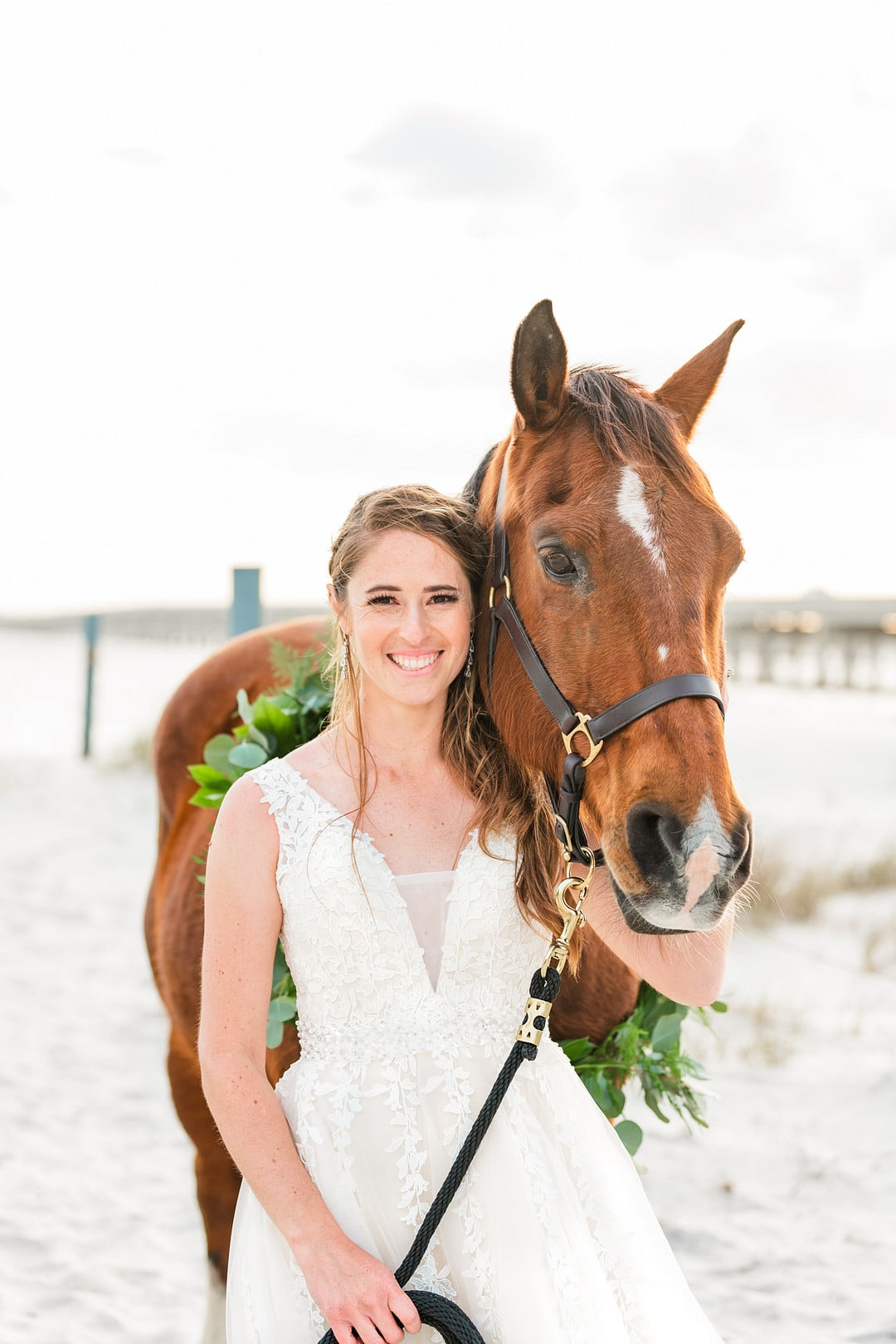 bride smiling next to her horse on the beach at amelia island