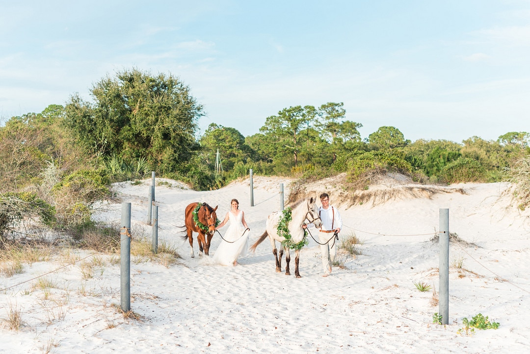 the bride and groom walking their brown and white horses down to the beach
