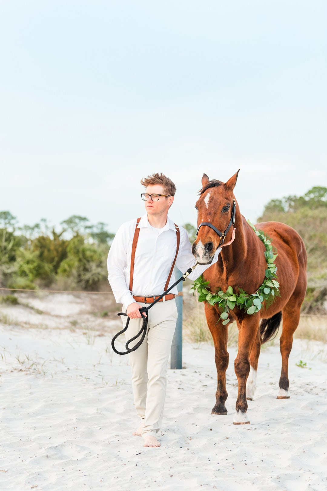 the groom walking his brown horse to the beach at amelia island