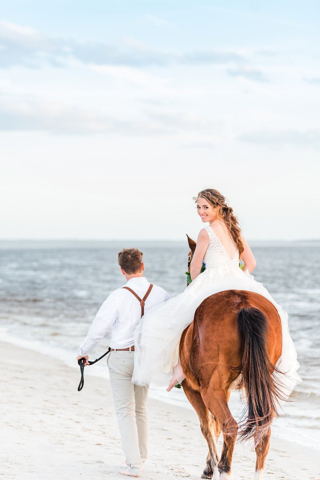 bride riding her horse and looking back while groom walks the horse