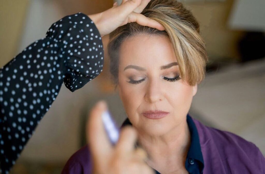 woman closing her eyes as About Face Design Team works on her makeup