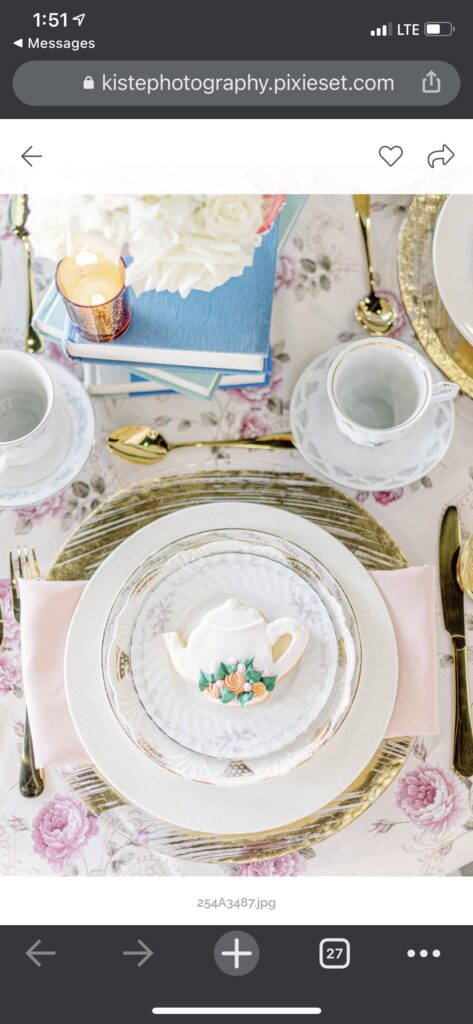 table set up with fine china and cookie that looks like the dishes