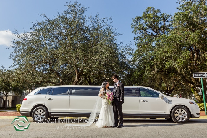 bride and groom standing outside of a stretch white limousine.