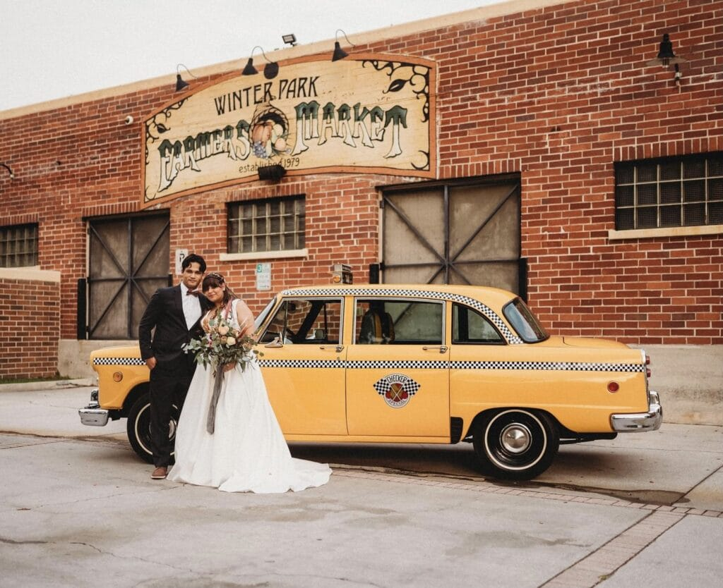 bride and groom standing next to a classic yellow taxi cab