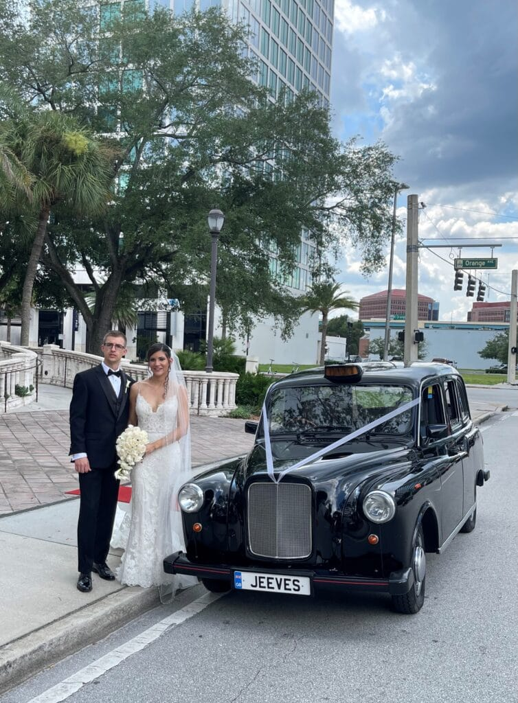 bride and groom standing next to classic black car with Great Britain tags