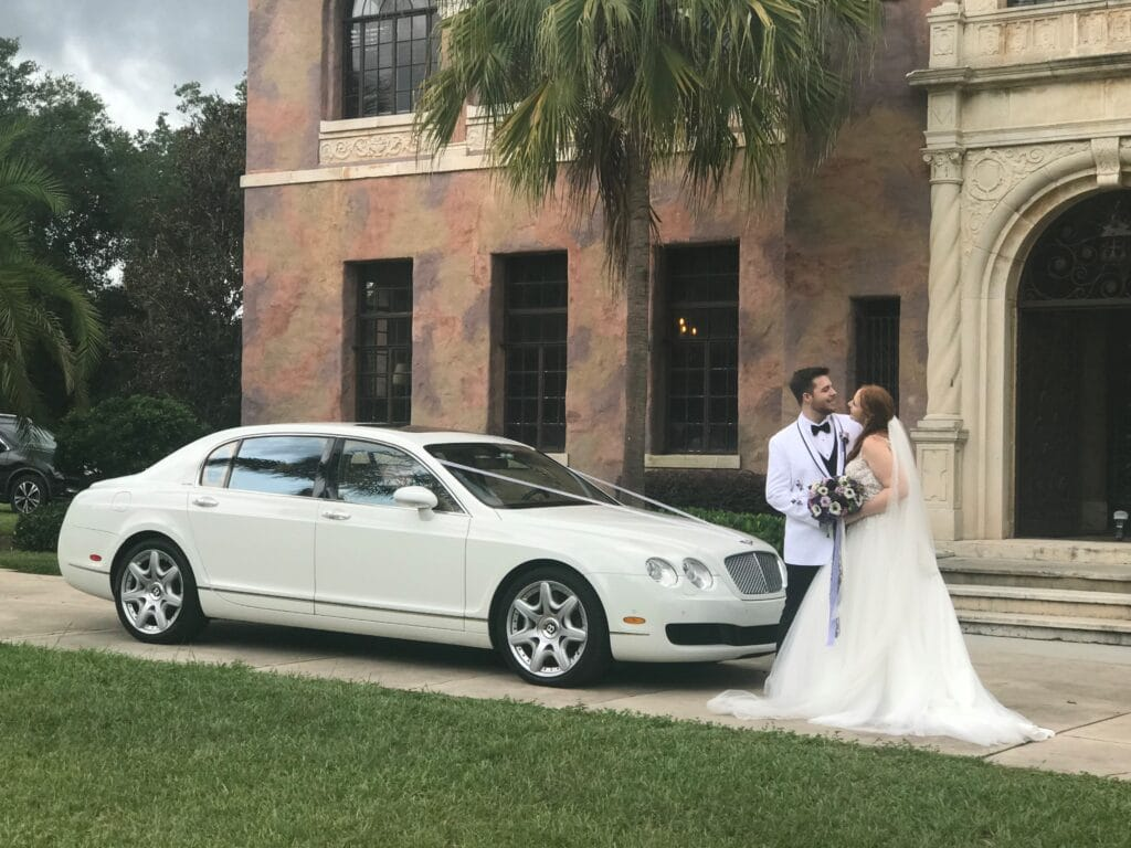 bride and groom standing in front of white car