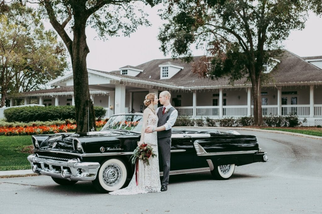 bride and groom kissing in front of classic black convertible