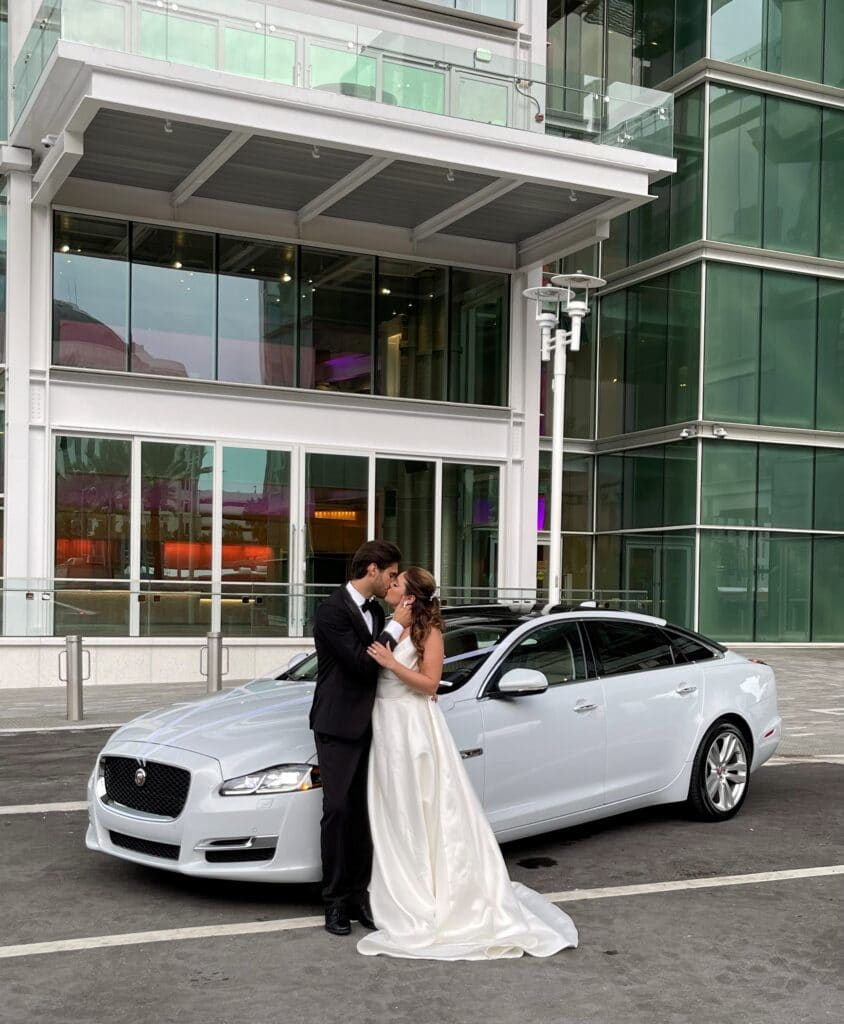 bride and groom kissing in front of luxury car