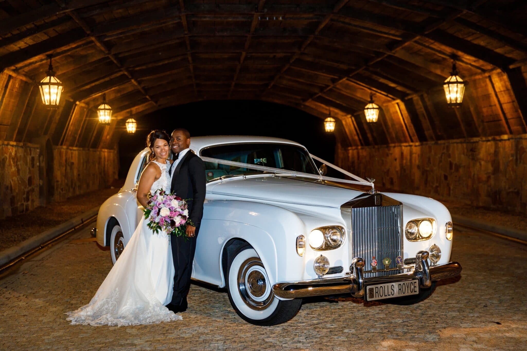 bride and groom standing in a tunnel next to a classic white Rolls Royce