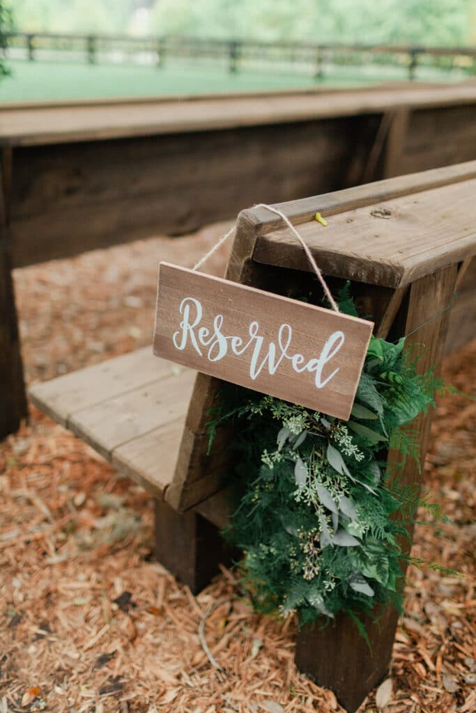 flower decorations behind reserved seating sign for wedding ceremony