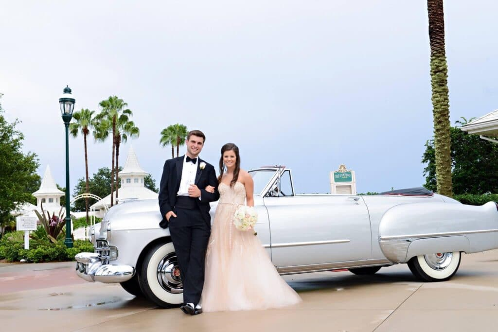 bride and groom leaning against classic grey convertible car