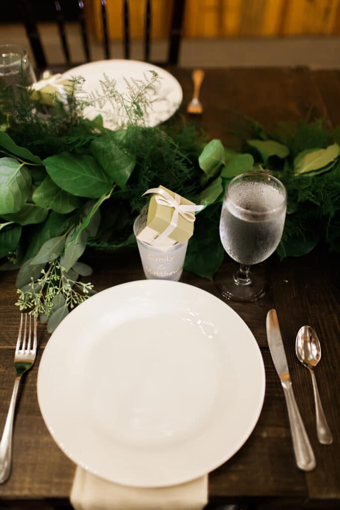 table set up for wedding reception with decorations and green and white flowers in the middle of the table
