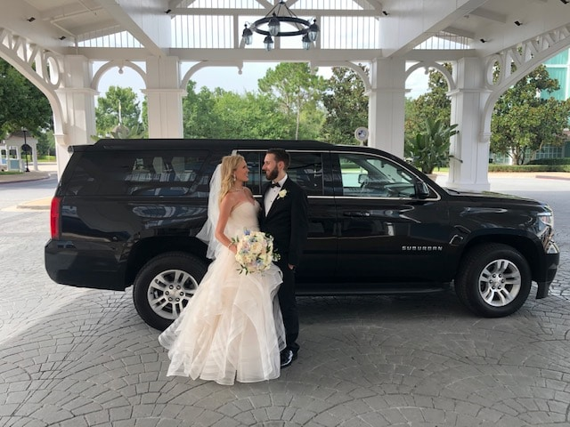 bride and groom standing next to large black Suburban suv
