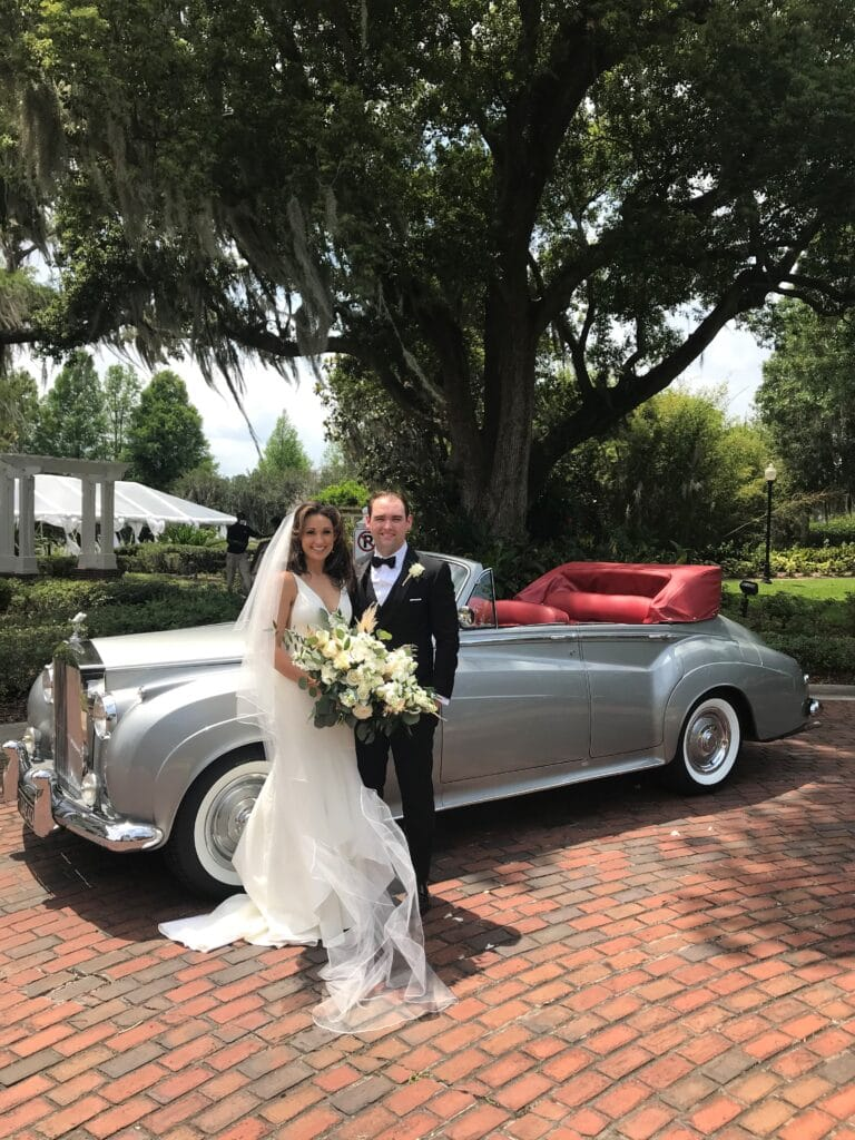 bride and groom standing next to a classic grey convertible car