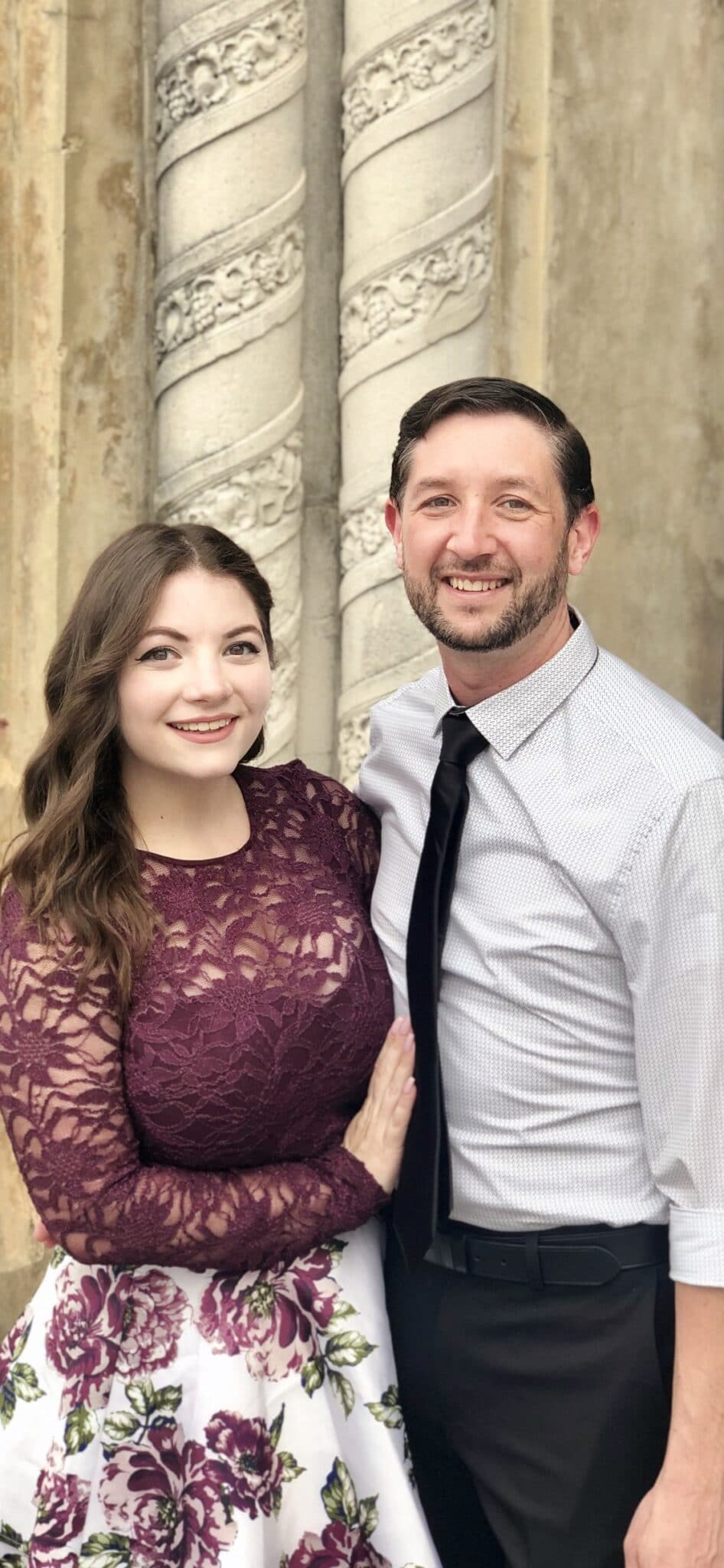 bride and groom to be standing together in dress clothes and smiling