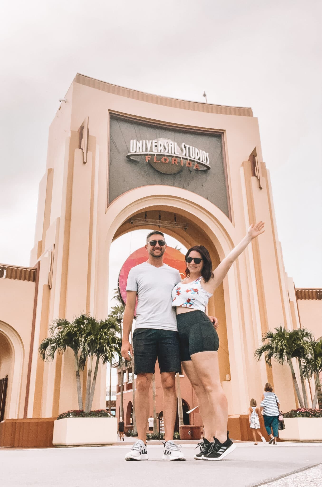 the couple standing outside of universal studios with the bride to be holding her arm out