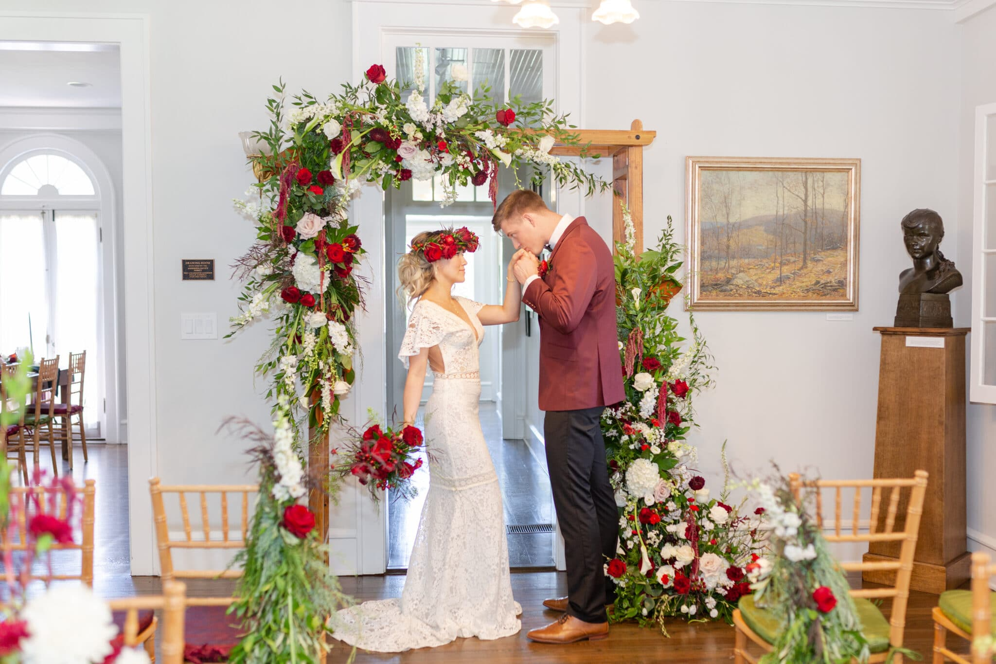 groom kissing his bride on her hand while standing a the alter decorated with red, green and white flowers for the christmas themed wedding inspiration shoot