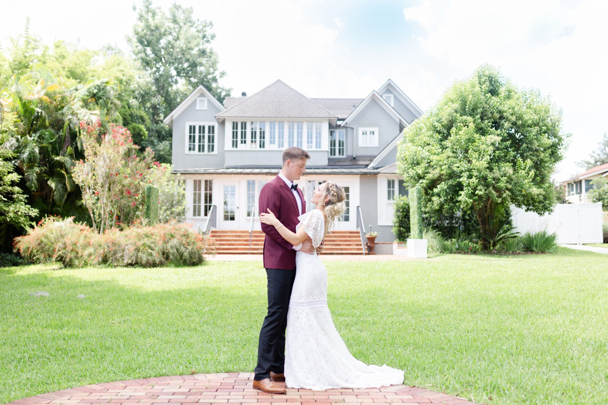 married couple holding each other in front of the capen house which is the venue of the christmas themed wedding inspiration shoot
