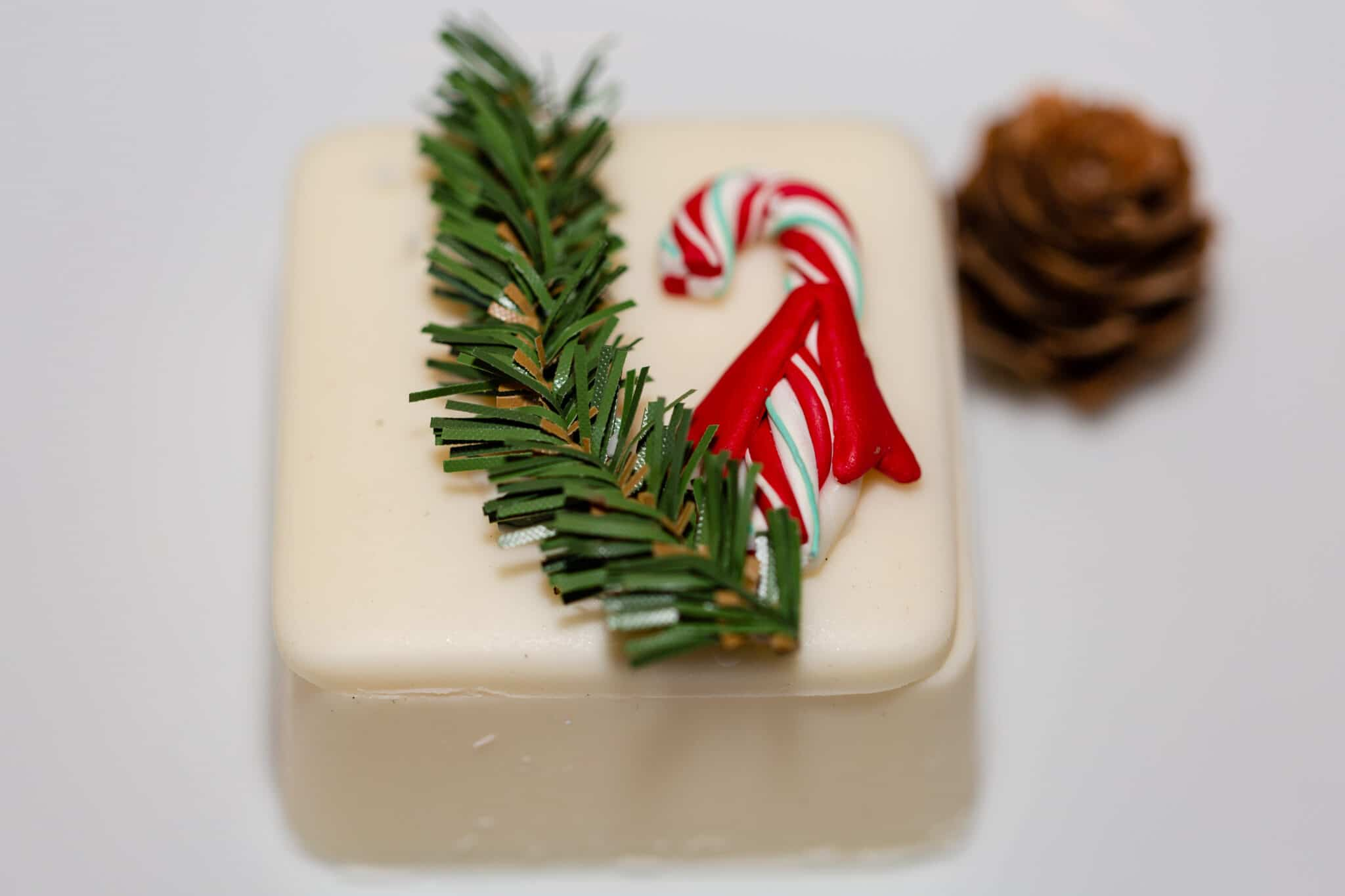 a white chocolate square decorated with greenery and a small candy cane for Christmas themed wedding inspiration