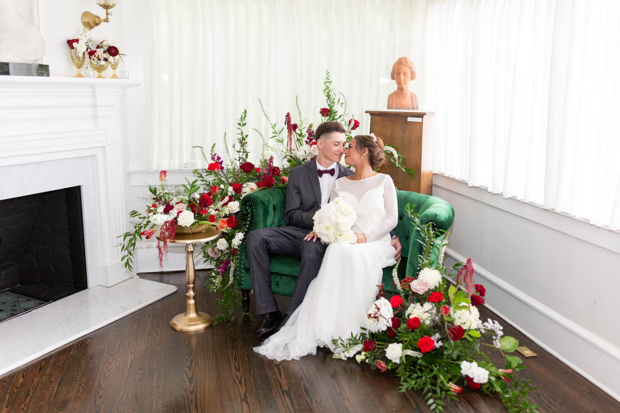 Christmas themed wedding inspiration green velvet sofa surrounded by Christmas florals